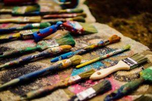 Kuvassa on maalarin työkaluja, lähinnä erilaisia siveltimiä.
