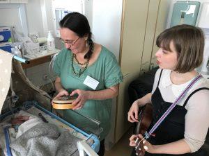 Kuvassa on kaksi muusikkoa ja aivan pieni vauva.