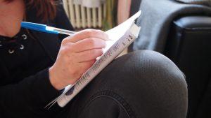 Kuvassa kirjoitetaan käsin paperille, jonka alla on kirja.