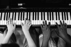 Kuvassa soitetaan pianoa kaksikätisesti.