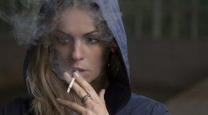 Kuvassa on nainen, joka tupakoi.