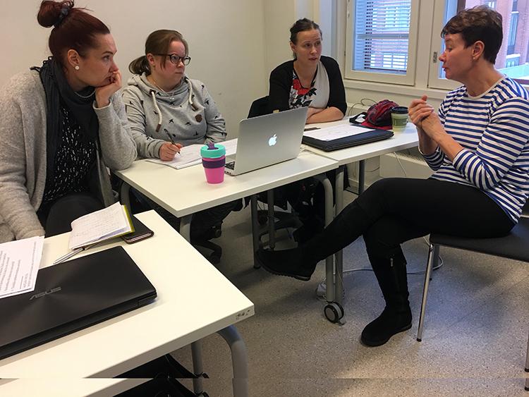 Opiskelijaryhmä keskustelee asiakkaan kanssa.