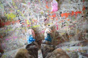 Kuvassa ovat näkyvillä ylhäältä alaspäin kuvatut taiteilijan jalat. Housut ja kengät ovat peittyneet maaliroiskeisiin, samoin lattia jalkojen alla.