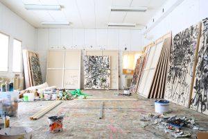 Kuvassa avautuu taiteilijan työhuone, jonka seiniin nojaa isokokoisia maalauspohjia.