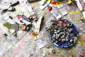Kuvassa on tyhjäksi puristettuja maalituubeja sekä lautalsellinen maalituubin korkkeja.
