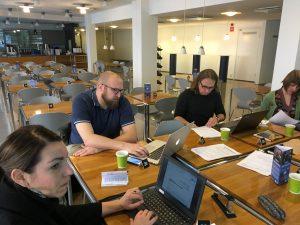 Tiimi eli neljä ihmistä työskentele pöytien ääressä edessään kannettavat tietokoneet.