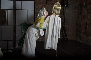 Kuvassa on nainen pyyhe ympärillään, hän ojentautuu kohti hahmoa, joka muodostuu kylpytakista ja lintuhäkistä.