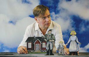 Kuvassa on nukettaja Timo Väntsi ja hänellä edessään paperinen talo sekä kolme nukkehahmoa.