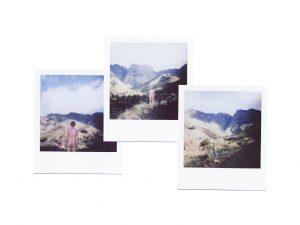 Kuva koostuu kolmesta polaroid-kamerakuvasta, joissa näkyy vuoristomaisema ja kahdessa kuvassa alaston henkilö takaa päin.