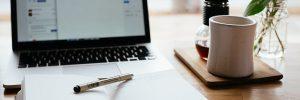 Työpöydällä muitsio, kynä ja kannettava tietokone