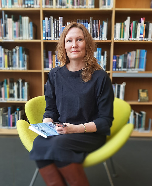Kati Lahtinen istuu kirja sylissä.