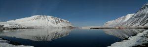 Kuvassa näkyy islantilainen maisema lumisine rinteineen. Sininen taivas ja lumiset rinteet heijastuvat järven pinnalla.