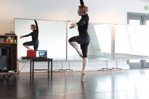 Kuvassa on tanssija liikkeessä. Kuva hänestä heijastuu myös seinän peilistä ja pöydällä olevalla läppärin näytöllä.