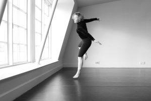 Kuvassa on tanssija liikkeessä suuren ikkunan äärellä.