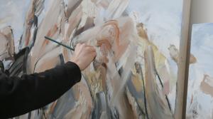 Kuvassa näkyy maalaava käsi, jossa on sivellin, sekä taustalla maalaus, jota taiteilija työstää.