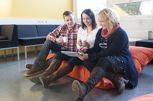 Mies ja kaksi naista katsovat läppäriä kahvitauolla.