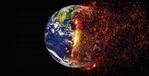 Kuvassa on maapallo, jonka vasen puoli on tavallisen näköinen ja oikea puoli hajoamass tuliseksi usvaksi.