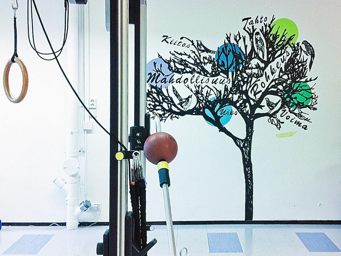 Kuvassa näkyy seinämaalaus fysikaalisen hoitolaitoksen seinällä. Maalauksen edessä on laite fysikaalista harjoitetta varten.