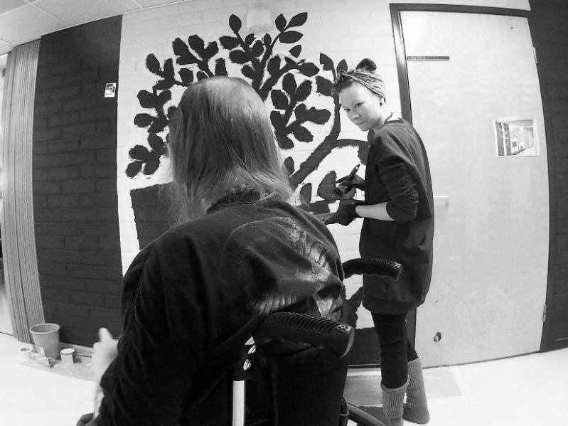 Kuvassa on taitelija Heli Mannisenmäki ja asukas seinämaalauksen äärellä.