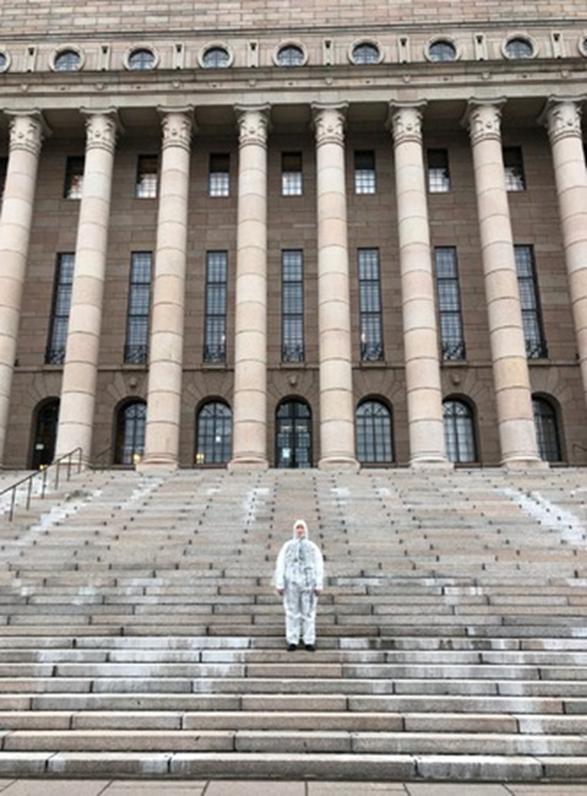 Kuvassa on suoja-asuun pukeutunut hahmo Eduskuntatalon portailla.