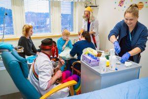 Kuvassa on kaksi klovnitohtoria töissään. Lisäksi kuvassa on kaksi hoitajaa, lapsi ja luultavasti lapsen äiti tai muu tutkihenkilö.