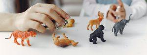 Etualalla leluja pöydällä, taustalla naisen ja lapsen kädet.
