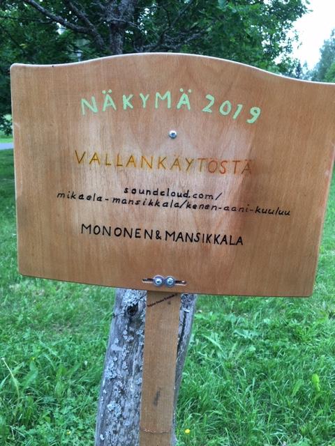 Kyltti Näkymä 2019 -ympäristötaidefestivaalilta. Teoksessa mainitaan Monosen ja Mansikkalan teos.