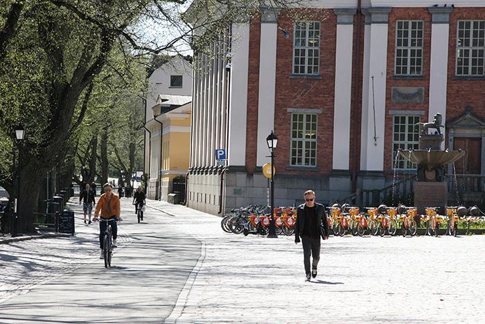 Kävelijöitä ja pyöräilijöitä kadulla.