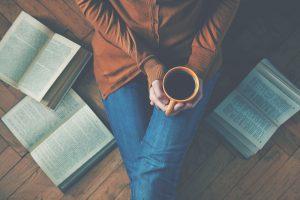 Kuvassa henkilö istuu kirjojen ympärillä kahvikuppi käsissään