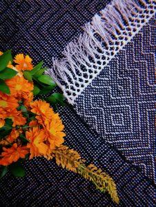 Kuvassa on matto ja oransseja kukkia.