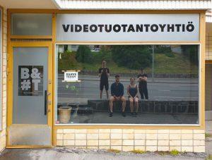 Kuvassa näkyy videotuotantoyhtiö Brave Teddyn nimi sekä neljä työntelijää heijastuneina yhtiön toimitilan ikkunasta ulkoapäin kuvattuna.