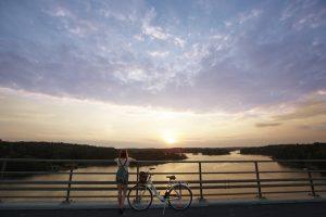 tyttö, polkupyörä, saaristomaisema sillalta