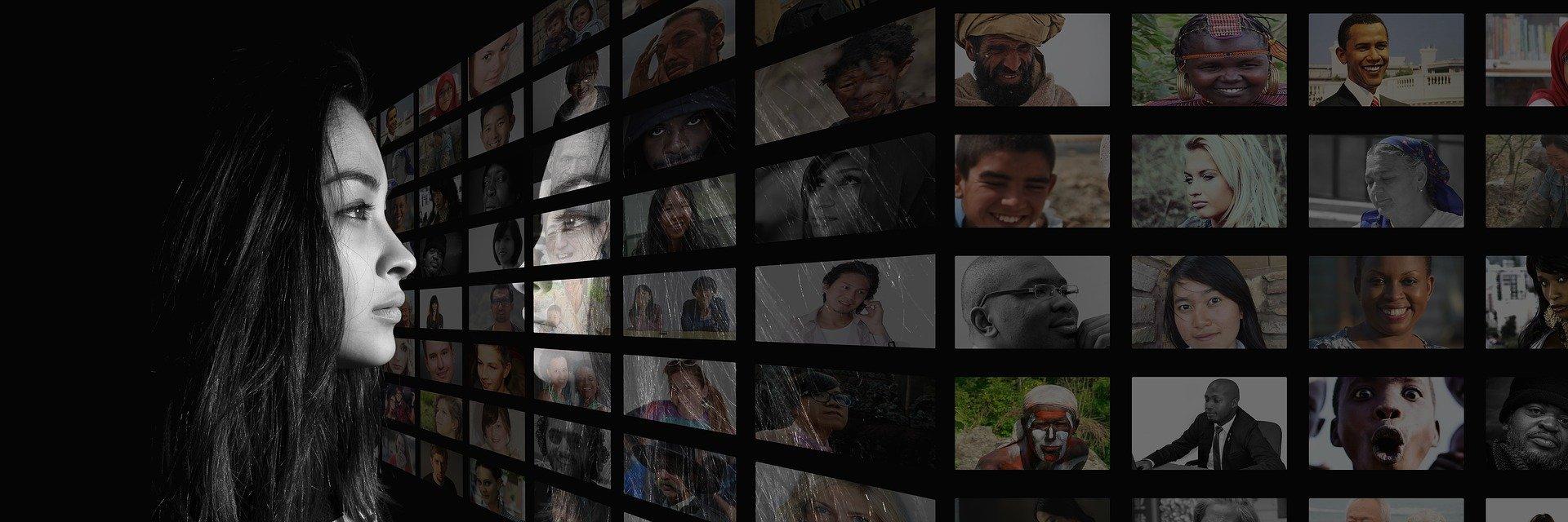 Kuvassa henkilö katsoo näyttöseinää, jossa on monien ihmisten kasvokuvat ruudulla.