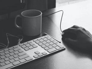 Tietokoneen näppämistö, käsi hiirellä ja kahvimuki.