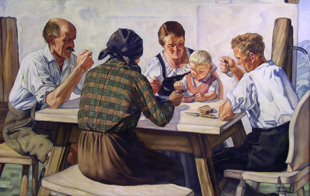 Kuvassa perhe ruokailee pöydän äärellä. Äiti syöttää lasta. Pöydällä on pala leipää ja veitsi.