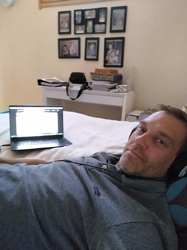 Olli tekee vuoteella töitä, takana tietokone.
