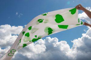 Kuvassa liehuu kangas, jossa on vihreitä sydämiä. Tausatalla on sininen poutapilvinen taivas.
