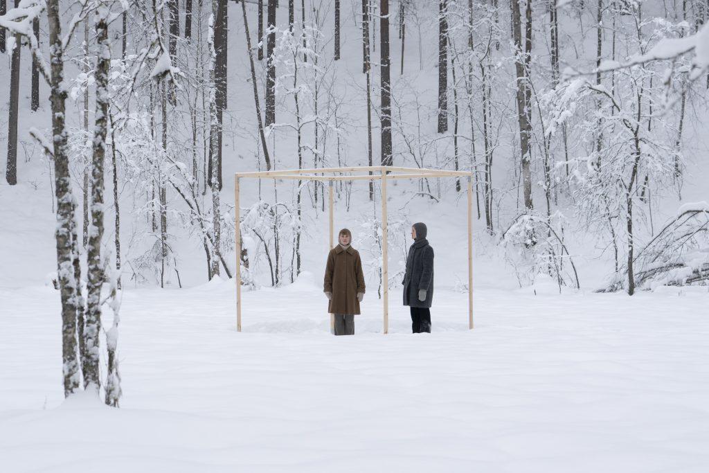 Kuvassa on kaksi ihmishahmoa talvisessa maisemassa taustanaan metsä. Hahmot seisovat puusta tehdyn kehikon tuntumassa.