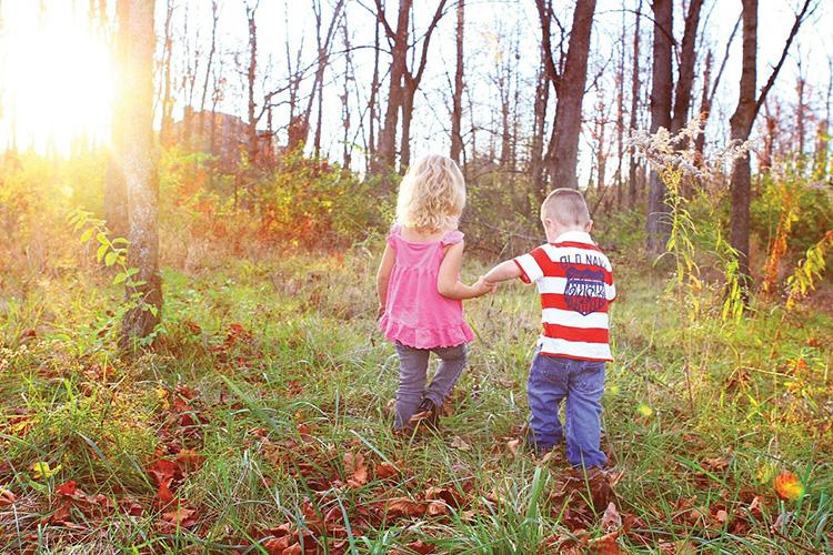 Pieni tyttö ja poika kävelevät käsikädessä ulkona.