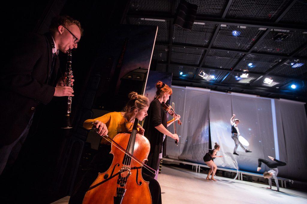 Kuvassa on näkyvillä kolme muusikkoa soittamassa sekä kolme akrobaattia taiteilemassa taustalla.
