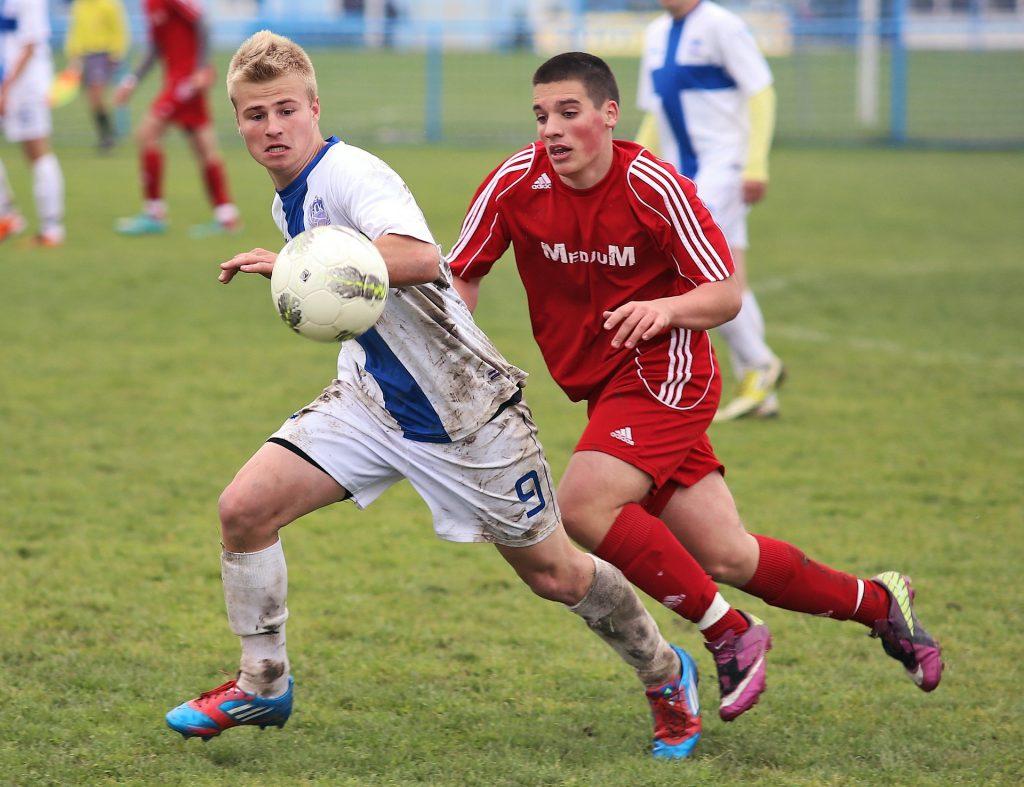 Kuvassa on kaksi nuorta miestä ja jalkapallo ilmassa, pellajilla keskittyneet ilmeet ja pelissä likaantuneet vaatteet.