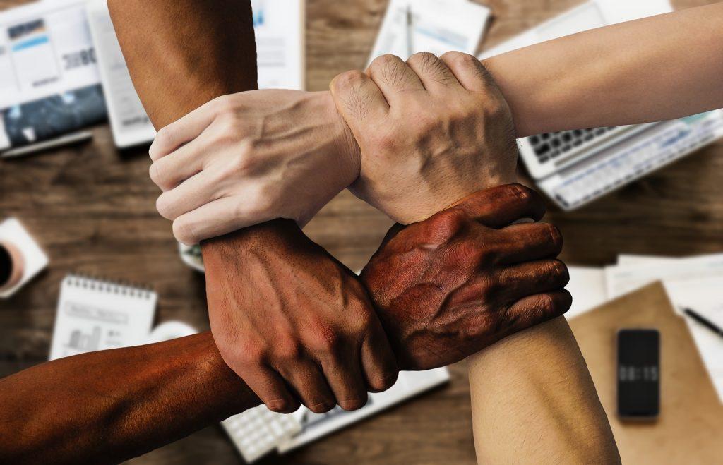 Kuvassa on neljän ihmisen kädet toisistaan otteen ottaneina. Taustalla on toimiston pöytä kännyköineen, tietokoneineen ja lehtiöineen.
