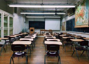 Kuvassa on luokkahuone, jossa pulpetit ovat rivissä mutta ketään ei ole paikalla.