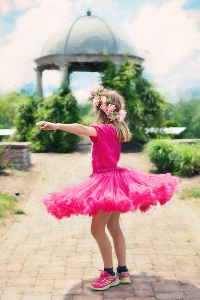 Kuvassa on lapsi kukkaseppel päässään, pinkki asu, leveähelmainen hame päällään.