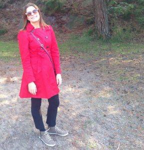 Nainen punaisessa takissa seisoo ulkona.
