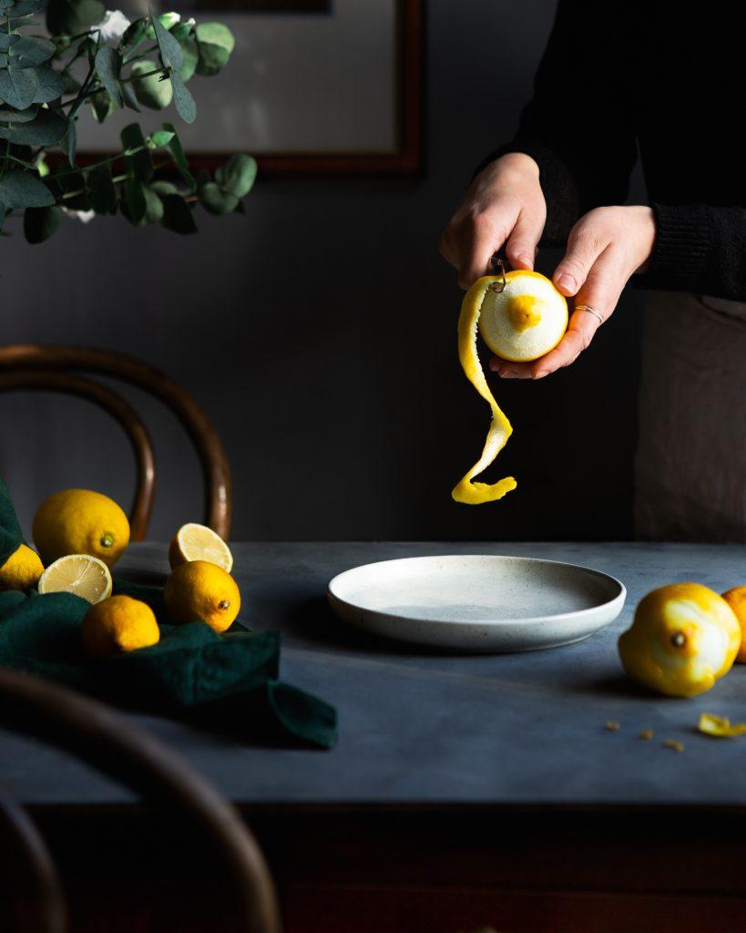 Kuvassa on sitruunoita pöydällä sekä kädet kuorimassa sitruunaa.