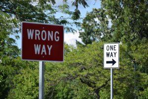 Kuvassa on näkyvillä puita sekä kaksi kylttiä, joista toisessa, puhaisessa, kulee wrong way, ja toisessa, valkoisessa one way.