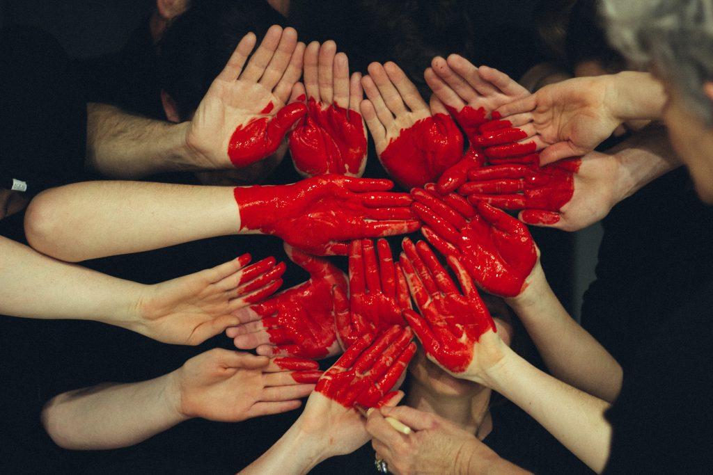 Kuvassa on monia käsiä kämmenet katsojaan päin. Niihin on maalattu punainen sydän.