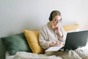 nuori nainen istuu sohvalla, tekee muistiinpanoja paperille ja tietokoneelle