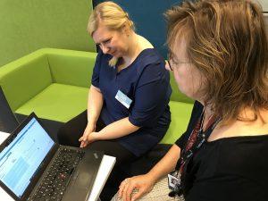 Kaksi naista, opettaja ja ohjaaja tietokoneen ääressä.